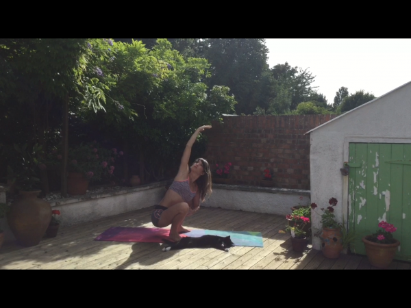 Malasana with side stretch in a pretty English garden