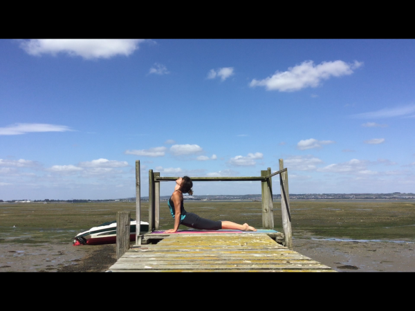 Upward facing dog at the end of a jetty on a summers day