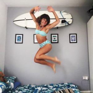 surfer girl jumping for joy